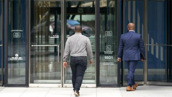 People enter an office building in downtown Dallas, Texas, U.S., on Wednesday, May 27, 2020. Texas Governor Greg Abbott allowed bars along with rodeos, bowling alleys and bingo halls to open their doors at reduced capacity in the second phase of the states plan to restart the economy after shutting down in early April to slow the coronavirus. Photographer: Cooper Neill/Bloomberg via Getty Images