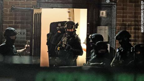 Armed police officers work at a block of flats in Reading after an incident at Forbury Gardens park in the town centre of Reading, England, Saturday.