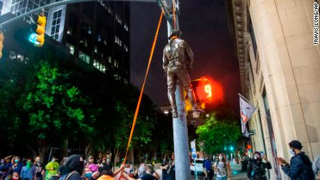 Protesters hang a figure pulled from the Confederate monument at North Carolina's State Capitol Friday.