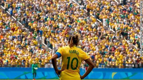 Brazil's player Marta stands facing the Brazilian crowd.