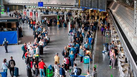 Travellers wait to check in for a flight from Frankfurt, Germany to Mallorca, Spain.