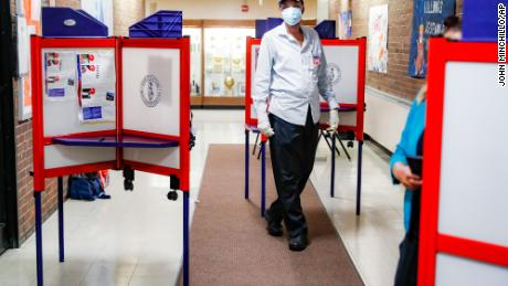 A polling worker walks among voting booths at a voting site inside Yonkers Middle/High School, Tuesday, June 23, 2020, in Yonkers, N.Y. (AP Photo/John Minchillo)