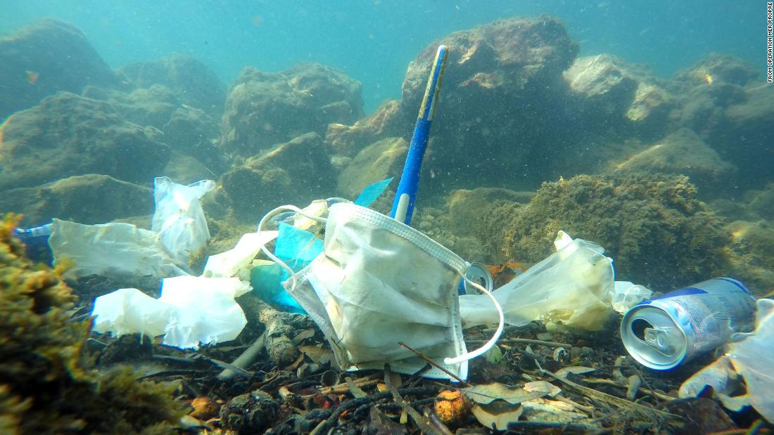 Gloves and masks are seen with other litter on the ocean floor.