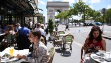 People have lunch at a restaurant near the Arc de Triomphe in Paris, France, on June 18.