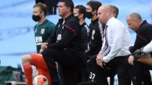 Managerul de la Burnley, Sean Dyche (dreapta) ia un genunchi în sprijinul mișcării Black Lives Matter.