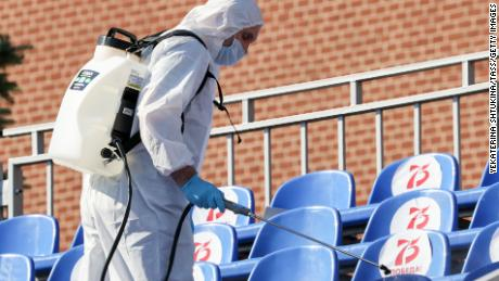 A sanitary worker in protective gear sprays disinfectant on seats in Red Square before the parade.