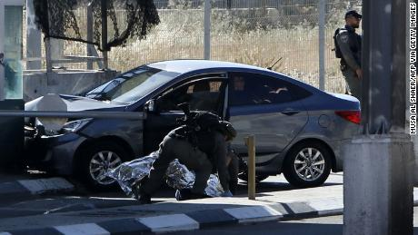 "Israeli security forces cover the body of Palestinian Ahmad Erakat, who was shot dead at the site of a reported ramming attack, at a checkpoint in the occupied West Bank near the village of Abu Dis on June 23, 2020. - A Palestinian man was shot dead at a checkpoint in the occupied West Bank after driving his car ""quickly"" towards a border officer, Israeli police said. (Photo by Musa Al SHAER / AFP) (Photo by MUSA AL SHAER/AFP via Getty Images)"