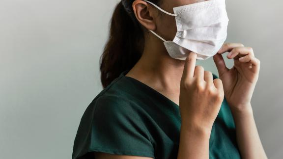 Hands close up woman wearing face mask. Studio shot masked woman staff putting mask on her face on grey background. Coronavirus or Covid-19 concept.