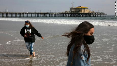 A mother and daughter  wear masks as they visit the beach Tuesday in Santa Monica, Calif.