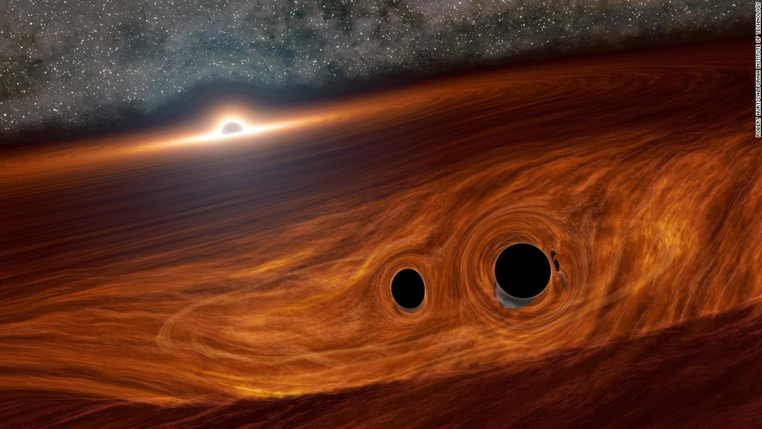 This is an artist's illustration of a supermassive black hole and its surrounding disk of gas. Inside this disk are two smaller black holes orbiting one another. Researchers identified a flare of light suspected to have come from one such binary pair soon after they merged into a larger black hole.