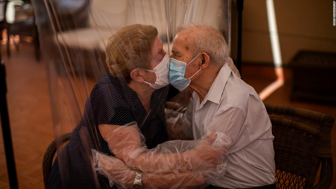 Agustina Cañamero and Pascual Pérez kiss each other through a plastic screen at a nursing home in Barcelona, Spain, on June 22. They've been married for 59 years.