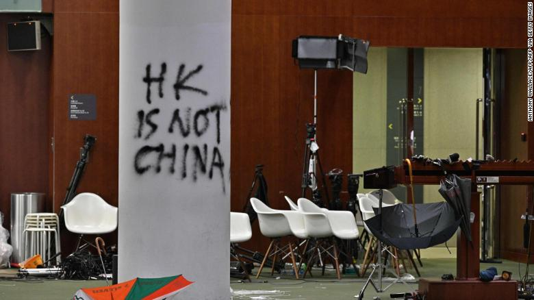 Graffiti and umbrellas are seen outside the main chamber of the Legislative Council during a media tour in Hong Kong on July 3, 2019, two days after protesters broke into the complex.