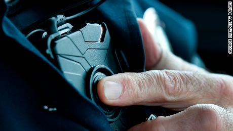 A West Valley City patrol officer in Utah starts a body camera recording by pressing a button on his chest.