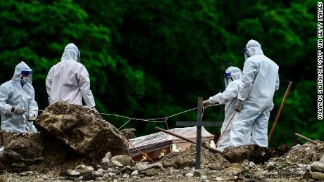 Men with protective gear bury a coronavirus victim in a cemetery 14 km north of Honduras & # 39; Capital, Tegucigalpa, June 21, 2020.