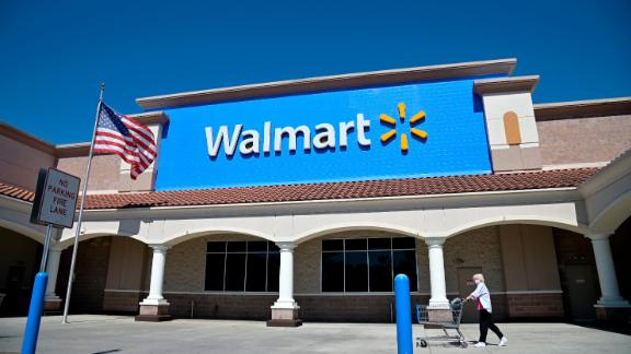 A Walmart customer pushes a cart to the store's entrance, Tuesday, May 19, 2020, in Orlando, Fla. Deemed an essential business, Walmart stores remained open during the new coronavirus pandemic. (Phelan M. Ebenhack via AP)