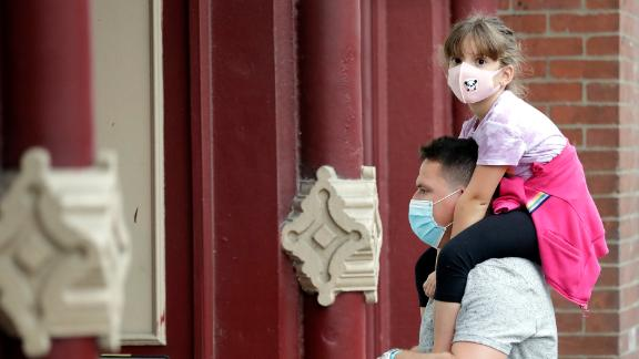 A man and a girl  hear a band outside a music venue in Nashville, Tenn. The Nashville Health Department has a mask mandate to help battle the spread of the coronavirus.