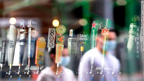 The reflection of pedestrians wearing facemeasks are seen as they walk past beer taps in a bar in Los Angeles on June 29, 2020 a day after the state's governor ordered the immediate closure of bars in a number of California counties, including Los Angeles County, due to rising spread of COVID-19 cases.ama