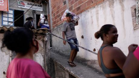 Residents carry food donated by a non-governmental agency amid the new coronavirus pandemic, in the Mandela slum, in Rio de Janeiro, Brazil, on  April 21