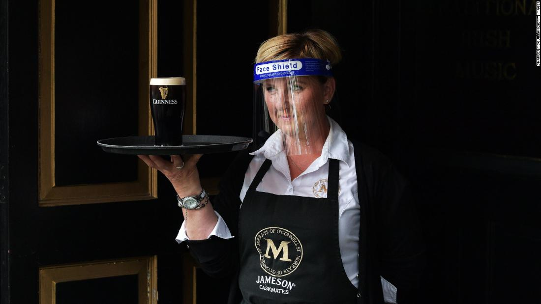 "A member of the bar staff at Murray's Pub serves a pint of Guinness in Dublin, Ireland, on June 29. People in Ireland are tentatively returning to shops, hair salons and restaurants <a href=""https://www.cnn.com/travel/article/ireland-reopens-blarney-stone-scli-intl/index.html"" target=""_blank"">as the country emerges from its coronavirus lockdown.</a>"