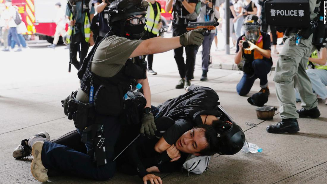 A police officer raises his pepper spray gun as he detains a man during a march on July 1.