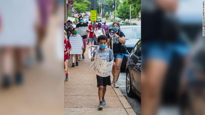 """Nolan Davis leading Saturday's protest with his poster that reads """"Kids can make a change."""""""
