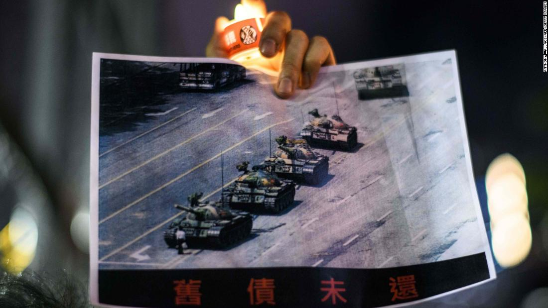 "A man holds up the iconic Tiananmen Square <a href=""https://www.cnn.com/interactive/2019/05/world/tiananmen-square-tank-man-cnnphotos/"" target=""_blank"">""Tank Man"" photo</a> during the Victoria Park rally."