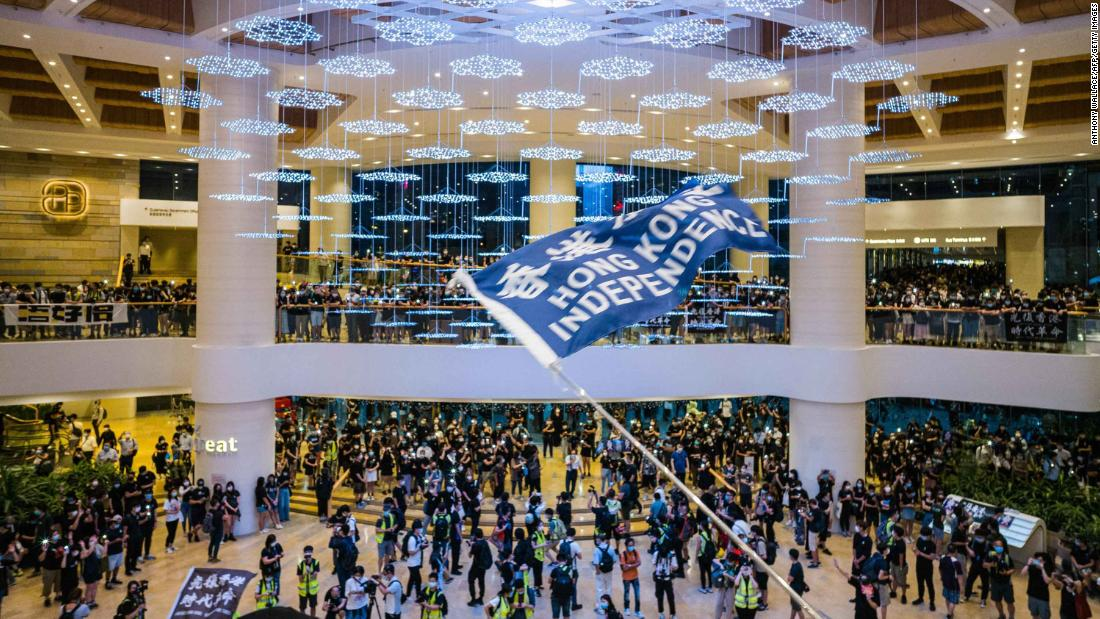 People wave flags and shout slogans inside a Hong Kong shopping mall on June 15.