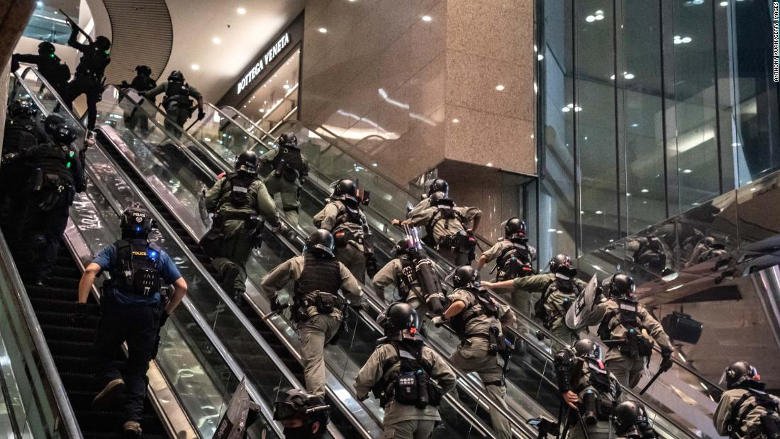 Police officers charge up shopping-mall escalators during demonstrations on July 1.