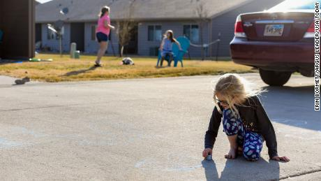 Lexus Larson, age 8, draws with sidewalk chalk outside her house while her friends, Maliah, 10, and Makinley Walsh, 7, play in their own yard across the street on Monday, April 6, in Sioux Falls, South Dakota.