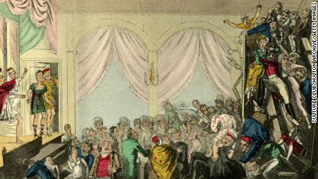 A riotious audience in the balcony during the  performance of a play in the early 19th century.