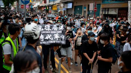 "Passers-by and protesters gather in Causeway Bay, Hong Kong. A protester is seen carrying a flag that says ""Liberate Hong Kong, revolution of our times,"" an act that could now be considered a crime under the city's new national security law."