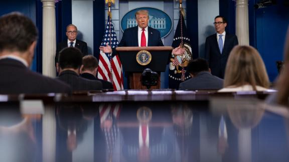 President Donald Trump speaks during a news briefing at the White House, Thursday, July 2, 2020, in Washington, as White House chief economic adviser Larry Kudlow, left, and Treasury Secretary Steven Mnuchin, look on.