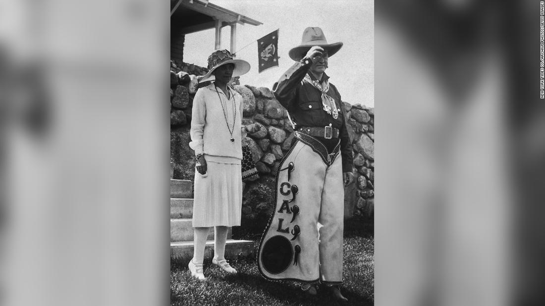 4th June 1927:  American president Calvin Coolidge (1872 - 1933) and his wife, First Lady Grace Coolidge (1879 - 1957), pose outdoors at a party celebrating the 4th of July and his 55th birthday at the Summer White House, State Game Lodge and Resort, Custer State Park, South Dakota. Coolidge is wearing a cowboy outfit, which includes a pair of personalized chaps.  (Photo by New York Times Co./Getty Images)