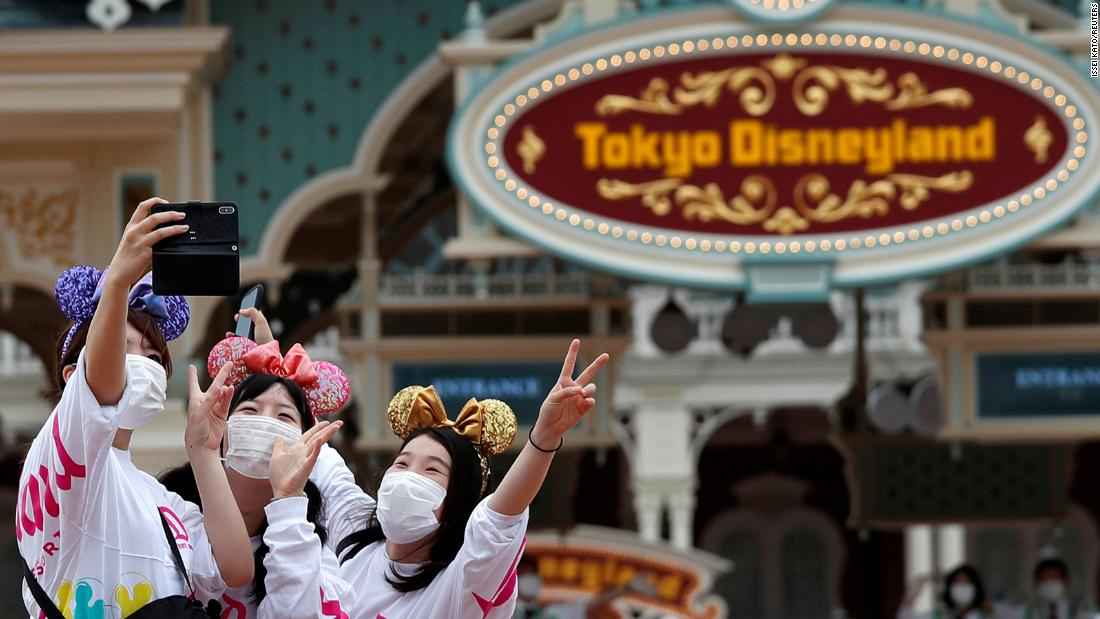 Visitors take a photo after the reopening of Tokyo Disneyland along with Tokyo DisneySea, which closed for months due to the coronavirus disease (COVID-19) outbreak, at the entrance gate of Tokyo Disneyland in Urayasu, east of Tokyo, Japan July 1, 2020.  REUTERS/Issei Kato     TPX IMAGES OF THE DAY