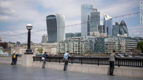 People observe social distancing as they look out at the view of the skyline of the City financial district from alongside Tower Bridge in London, on Tuesday June 9, 2020, following the introduction of measures to bring England out of lockdown. (Photo by Dominic Lipinski/PA Wire)