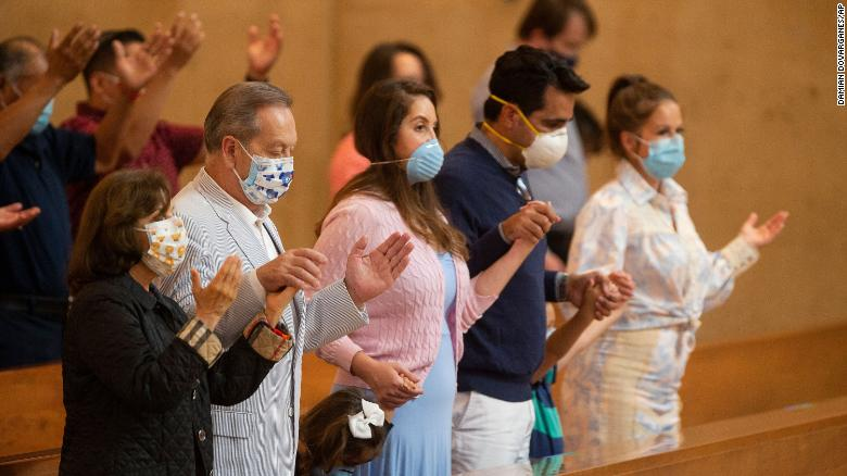 Family members hold hands as they pray at the first English Mass with faithful present at the Cathedral of Our Lady of the Angels in downtown Los Angeles on Sunday, June 7, 2020.