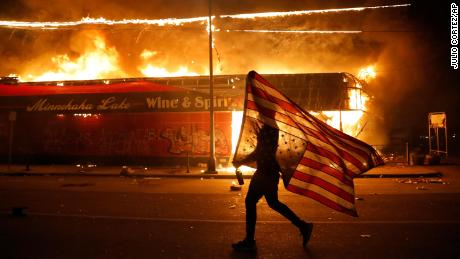 A protester carries a US flag upside down, a sign of distress, next to a burning building on May 28, 2020, in Minneapolis.