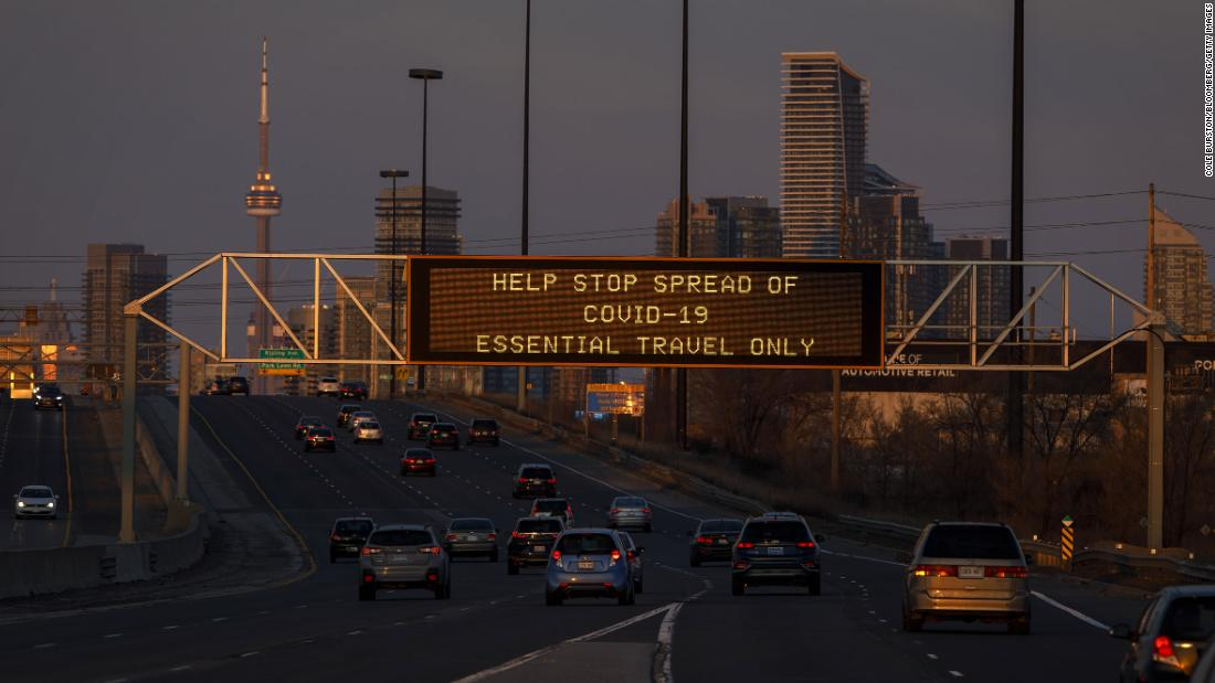 A digital sign telling motorists to limit travel during the coronavirus outbreak, is seen on a highway sign in Toronto, Ontario, Canada, on Saturday, March 21, 2020. The U.S. and Canada are poised to allow all those with work visas to continue to cross the border as the two countries hammer out details on new travel restrictions. Photographer: Cole Burston/Bloomberg via Getty Images