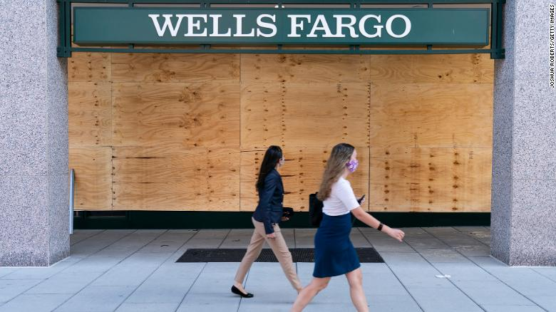Women walk past the boarded up branch of a Wells Fargo bank in in Washington, DC, last summer.