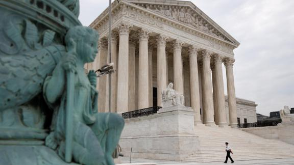 A police officer walks outside the Supreme Court on Capitol Hill in Washington, Monday, July 6, 2020.