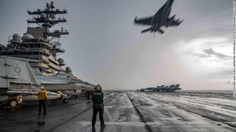 An F/A-18E Super Hornet flies over the flight deck of the USS Ronald Reagan in the South China Sea on July 4, 2020.