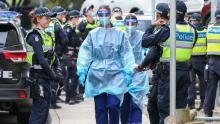 Medical staff wearing PPE walk into the Flemington public housing flats on July 5 in Melbourne, Australia after nine public housing estates were locked down.