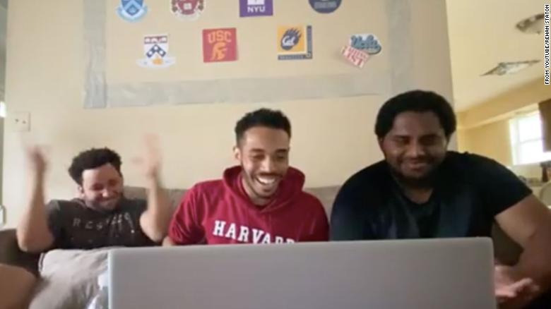 Rehan Staton, middle, with his cousin Dominic Willis, 24, left, and his brother, Reggie Staton, 27, at the moment he receives his acceptance to Harvard Law School.