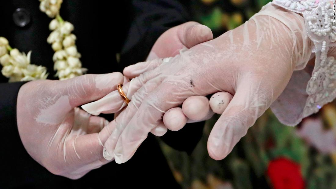 Octavianus Kristianto puts a ring on his new bride, Elma Divani, during their wedding ceremony in Pamulang, Indonesia, on June 19. They were wearing latex gloves to prevent the spread of the coronavirus.