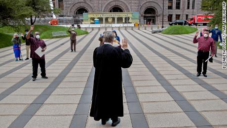 Chief Judge John R. Tunheim leads a group in the oath of allegiance during a naturalization ceremony at Federal Plaza in Minneapolis, Minnesota, on May 27.