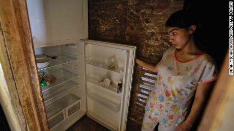 A Lebanese woman stands next to her empty refrigerator in her apartment in the port city of Tripoli north of Beirut on June 17, 2020. - Lebanon's economic crisis has led to a collapse of the local currency and purchasing power, plunging whole segments of the population into poverty as exemplified by near-empty fridges in many households. (Photo by IBRAHIM CHALHOUB / AFP) (Photo by IBRAHIM CHALHOUB/AFP via Getty Images)