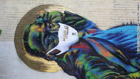 A street mural of Martin Luther King Jr. by Atlanta-based artist Fabian Williams is covered with a vinyl mask as part of the Covid-19 public awareness campaign Big Facts Small Acts.