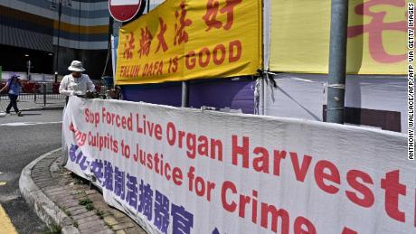 Une femme ajuste des banderoles pour soutenir le Falun Gong à Tung Chung, une zone populaire auprès des touristes du continent, à Hong Kong le 25 avril 2019.
