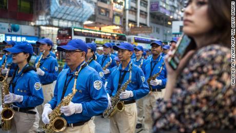 Une femme regarde les partisans du groupe spirituel du Falun Gong, interdit en Chine continentale, prendre part à une marche à Hong Kong le 27 avril 2019, pour observer le 20e anniversaire d'une grande manifestation à Pékin qui a conduit à une répression contre le mouvement .