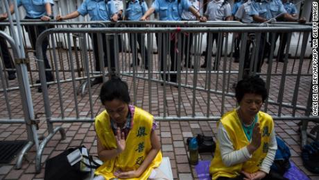 Les membres du Falun Gong méditent alors que les policiers regardent les manifestants lors d'une manifestation pro-démocratie à Hong Kong le 18 mai 2016.